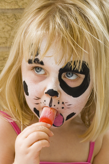 girl with painted face enjoys a popsicle
