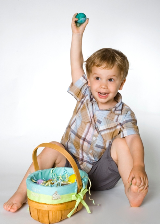 a boy with a painted egg and easter basket